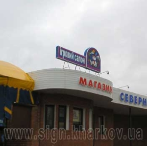 Световая двухсторонняя вывеска на крыше магазина